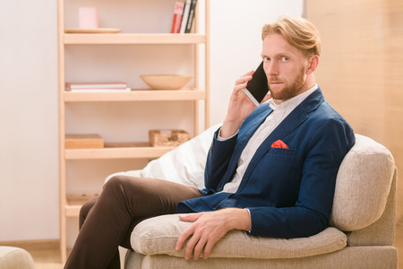 conceptions: Hnadsome rich European businessman using mobile or smart phone for talking with foreing business partners concerning new conceptions, strategies.
