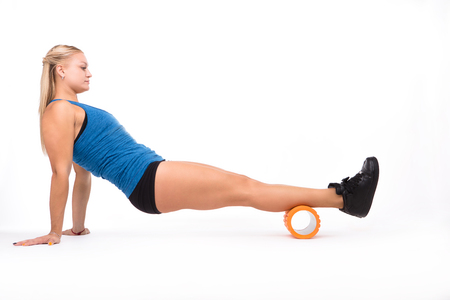 Picture of fitness woman stretching with help of massage device while training isolated on white background in studio. Massage concept.