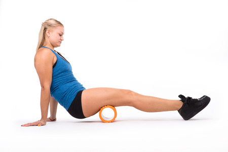 Health concept. Picture of fitness woman training with orange massage device isolated on white background in studio.