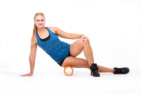 Picture of beautiful fitness woman training in studio. Happy blond lady stretching with help of massage device isolated on white background.