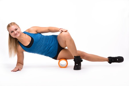 Picture of professional fitness trainer woman practicing with massage device while training isolated on white background in studio.