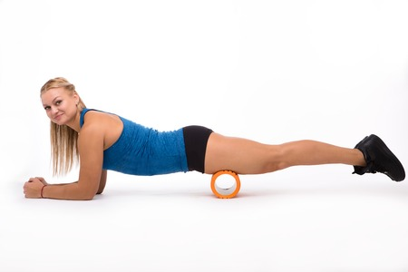 Picture of happy fitness woman doing push ups while training with massage device isolated on white background in studio.