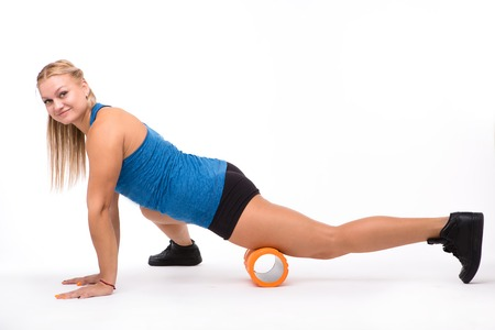 Happy sports lady training with massage device in studio. Fitness woman doing push ups while training isolated on white background in studio.