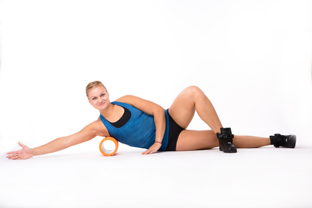 Fitness woman doing several exercises while training with massage device isolated on white background in studio. Health and fitness concepts.
