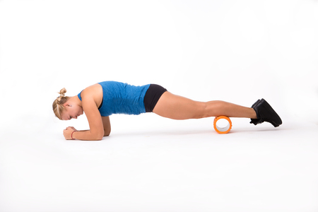 Fitness woman doing push ups in studio. Pretty woman using massage device isolated on white background. Health and fitness concepts.