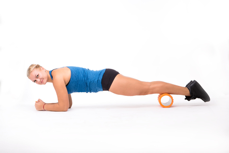 Happy sports and fitness woman doing push ups while training isolated on white background. Beautiful lady looking at camera while practicing.
