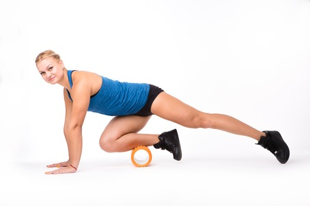 Picture of fitness woman looking at camera while training with massage device isolated on white background instudio. Health concept. Stock Photo