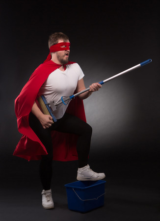 Super hero rock star playing guitar while posing for photographer. Super hero man ready for cleaning your office or house in studio. Stock Photo