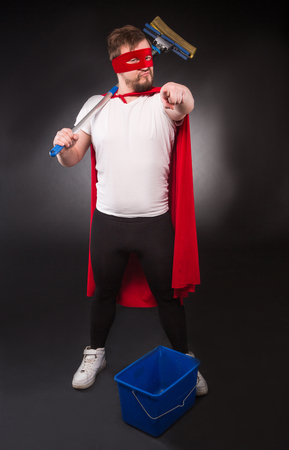 Cleaning concept. Super hero man ready to help your office or house with new cleaning equipment. Handsome man pointing to camera isolated on black background. Stock Photo