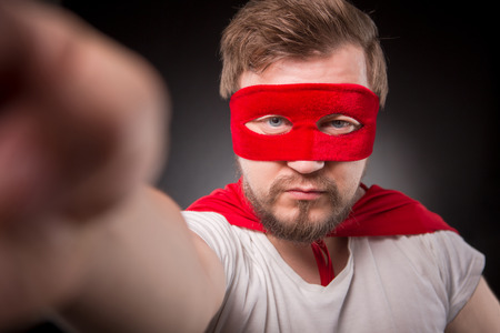 Egoist. Self. Hero. Super Hero. Closeup picture of super hero man with red mask on making photos isolated on black background in studio.