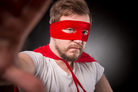 Egoist. Self. Hero. Super Hero. Closeup picture of super hero man in red mask looking at camera and making photos on mobile or smrt phone in studio.