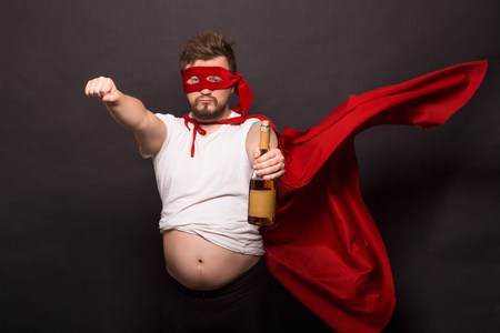Picture of bad super hero man showing bottle with wine while posing for photographer isolated on black background in studio.