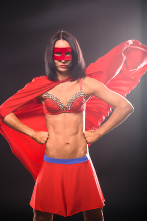 reincarnation: Young super hero woman isolated on black background in studio. Young confident woman in super hero costume. Stock Photo