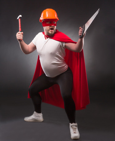 Picture of super hero man posing with hammer and saw isolated on black. Handsome man with red mask on screaming and shouting in studio.