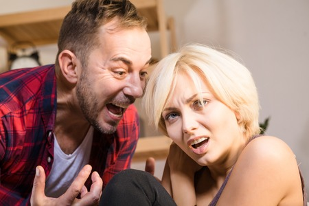 hugely: Closeup picture of couple man and woman having conflict at home. Divorce concept. Angry man screaming and shouting to his wife hugely. Stock Photo