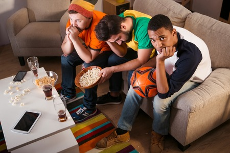gamers: Top view of sad friends watching football game on TV. Handsome man disappointed by game of their best football gamers. Stock Photo