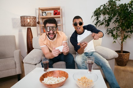 gamers: Happy friends playing computer games by using mobile phones. Handsome men looking at TV screen while sitting on sofa or couch at home. Stock Photo