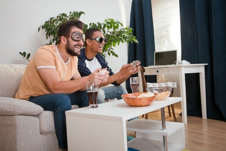 ard: Image of happy friends playing computer games with help of their mobile or smart phones after ard working day or week at home.