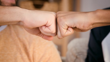 Closeup picture of two best friends mens wrists demonstrating unity and team work between two peoples from different countries.