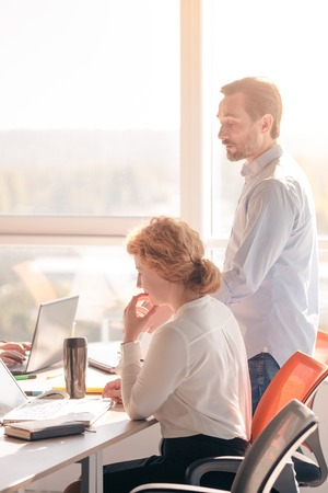 Business people working in board room in office all together. Businessman dictating to his worker woman business plans for future. Stock Photo