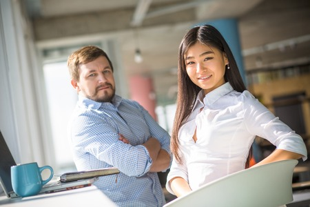 notion: Confident and executive businessman and businesswoman looking at camera and smiling while working in office interior. Business concept. Man posing with his arms crossed or folded.