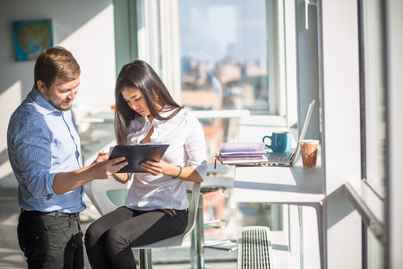 buisiness: Businessman and businesswoman looking at documentation of new business plan or strategy while working in office interior. Buisiness concept. Stock Photo
