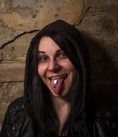 lsd: Funny girl taking LSD. Portrait of drug addict woman showing her tongue with rugs. Drugs concept. Stock Photo