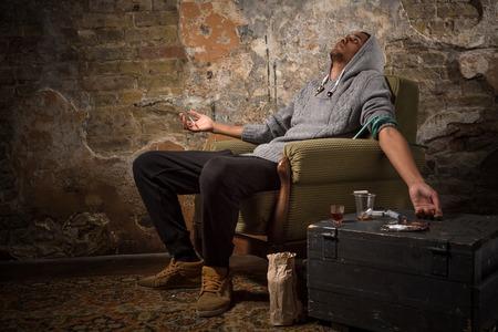 drogadicto hombre asiático en el trasero - zumbido capturado. El hombre sentado en la silla y dormir. concepto de drogas. concepto de narcóticos. Foto de archivo