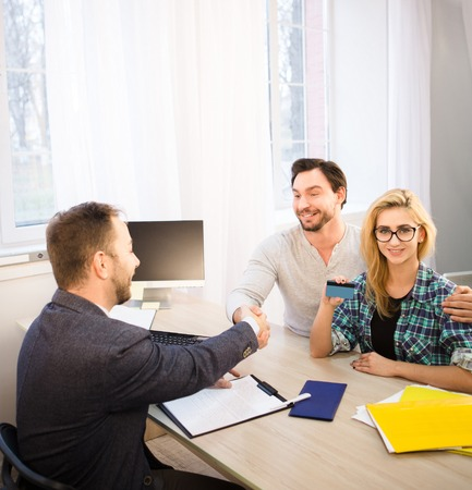 finance manager: Toned of happy bank officer and customer shaking hand after signing agreement or contract. Dealership concept. Bank concept. Money concept.