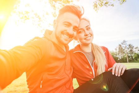 Sport man and woman making selfies in park