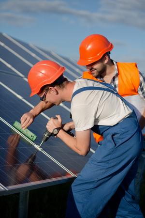 Technicians installing photovoltaic panels at solar power station. Archivio Fotografico
