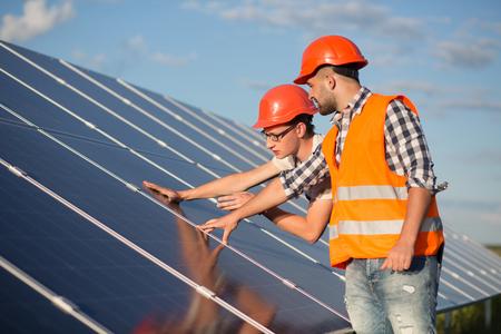 Werknemer en voorman onderhoud zonnepanelen. Stockfoto