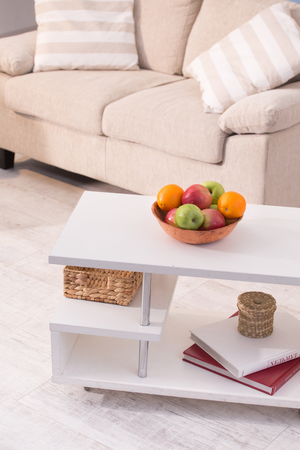 Close up view on cofee table with plate full of fruits,