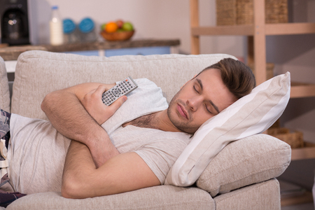 homeoffice: Lazy husband sleeping on couch while his wife at work. Stock Photo