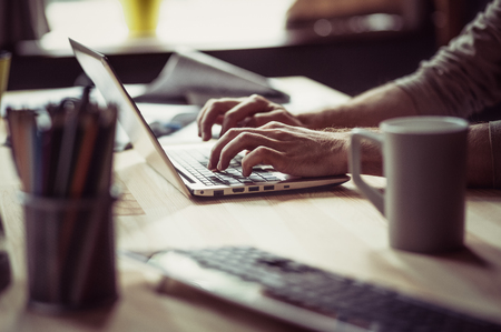 Side view on mans hands typing on computer.