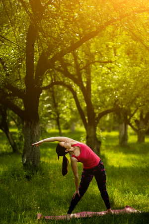 Young female practicing yoga in extended triangle pose. Stock Photo