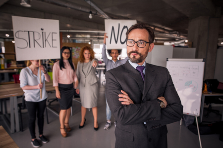 unsatisfied: Unsatisfied employees on strike in the office. Stock Photo