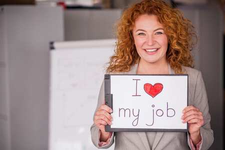 Red haired smiling businesswoman holding small poster. Stock fotó - 83748411
