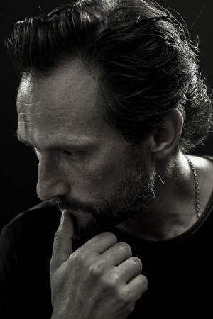 Black and white portrait of mid aged man showing suffering emotions.