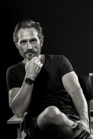 Black and white portrait of mature satisfied man sitting on chair.