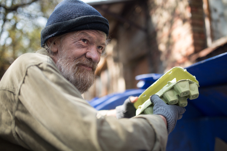 Dirty homeless man holding packing for eggs, standing by the trash can. Stock Photo