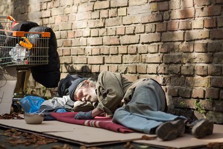 Slaap dakloze man liggend op karton. Stockfoto