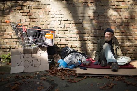 Homeles man sitting on ground in the strteet. Stock Photo