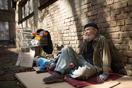 Homeless man sitting on cardboard by the brick wall.