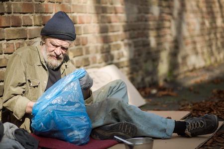 Weergave van een dakloze man snuffelen in vuilniszak. Stockfoto