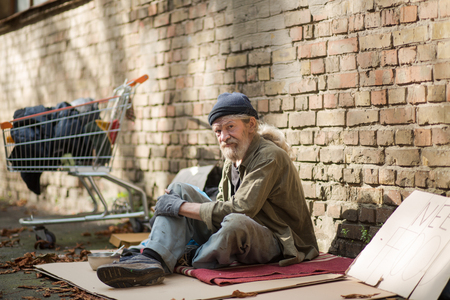 Side view of homeless man sitting on cardboard by the wall brick.