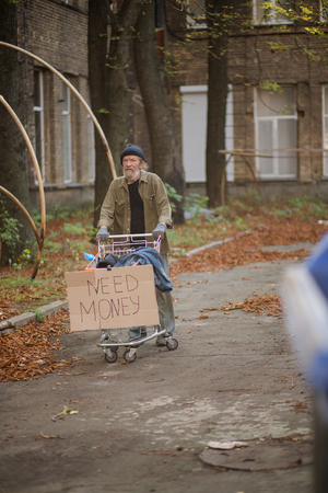 Hopeless old tramp with cart and board with sign need money.