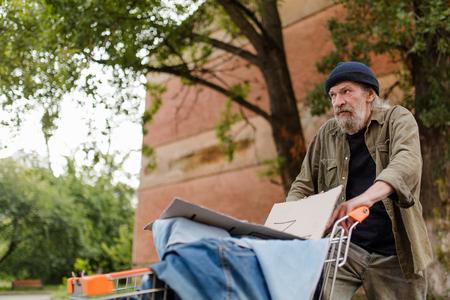 View of homeless man walking pushing shopping cart.