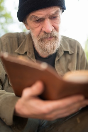 Close up portrait of old beardy man holding book in hands.