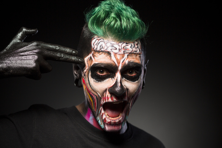 close up eyes: Halloween makeup, man with skeleton colored face touching temple. Face art. man with green hair and Halloween makeup isolated on black background. Stock Photo